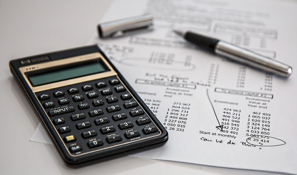 calculator and pen sitting on a financial statement