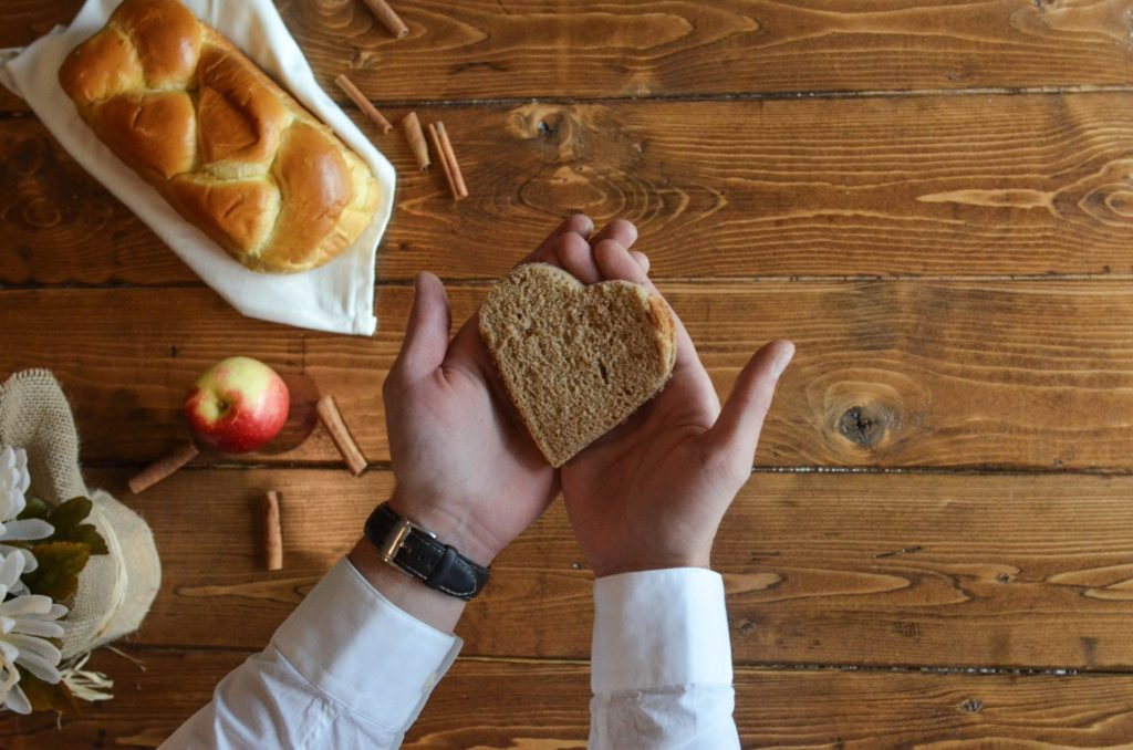 person holding heart shaped bread over table