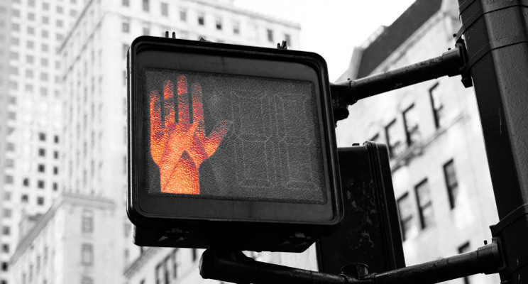 red hand indicating stop at crosswalk