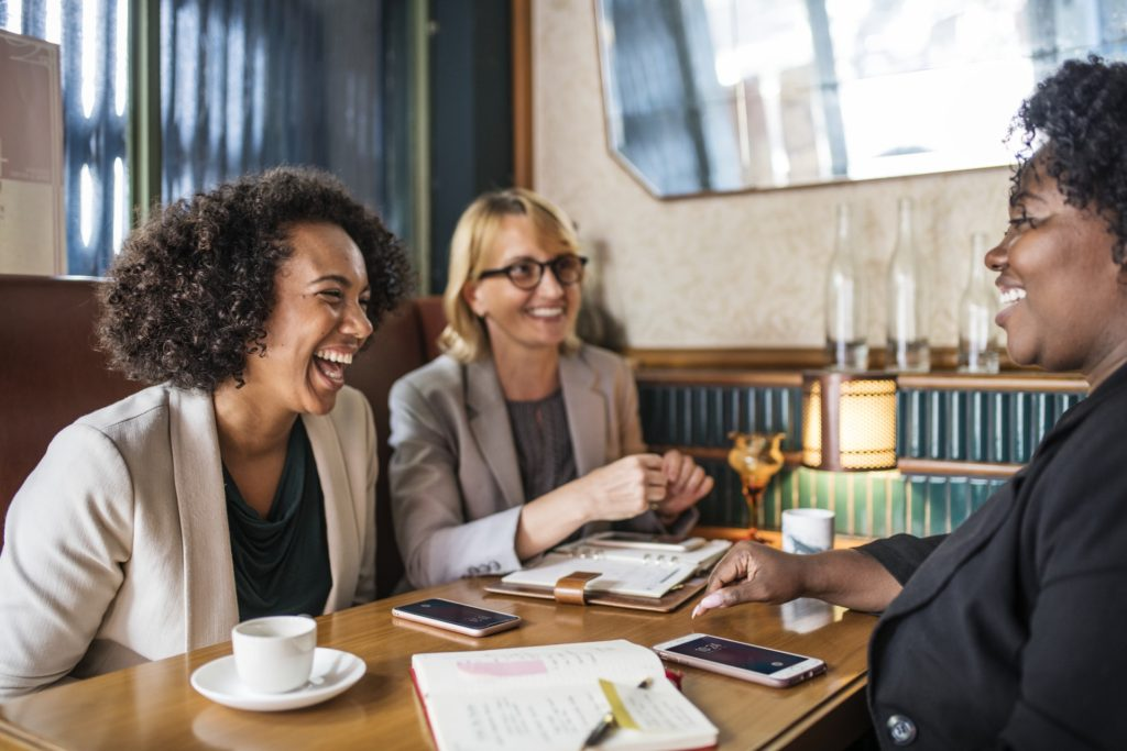 three smiling women seated at restaurant table