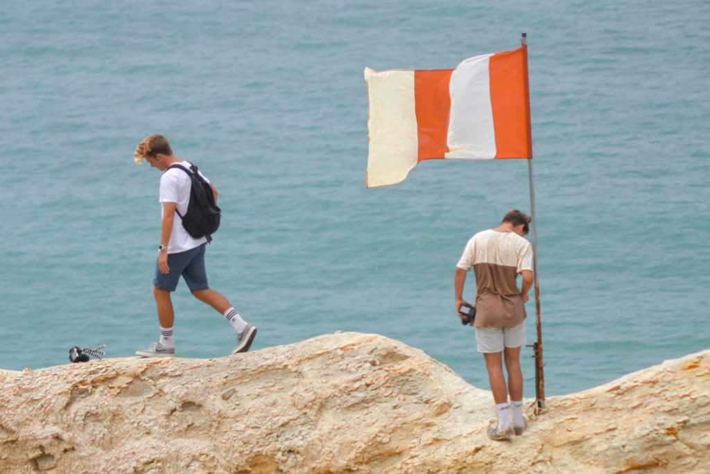 two men on a beach with flag