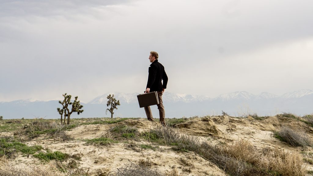 an elegantly dressed man with a suitcase in the wilderness