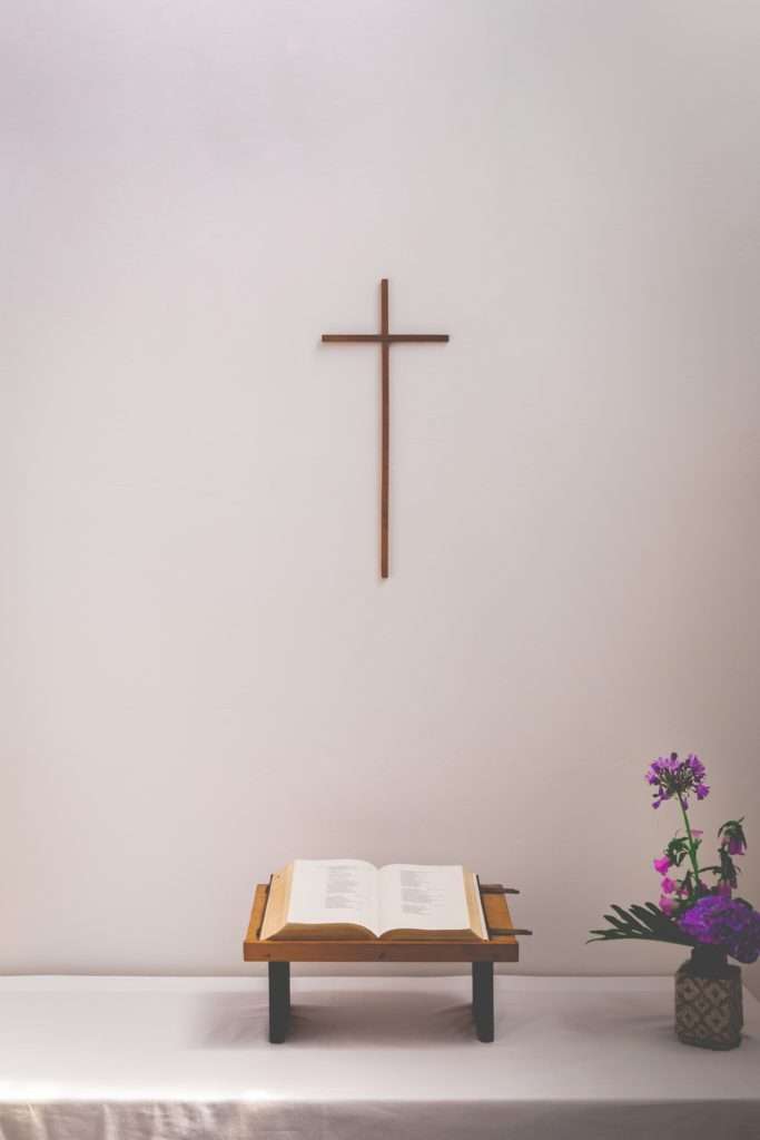 bible and flower on table under a cross