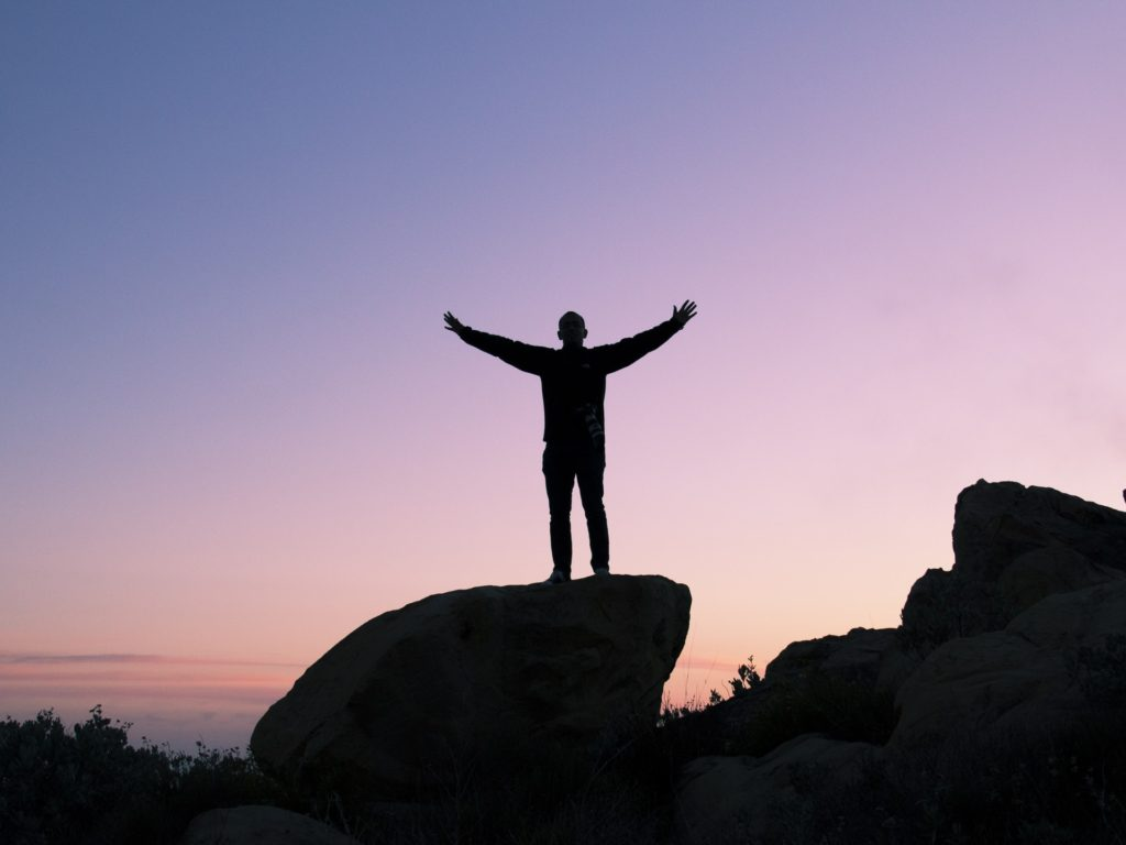 silhouette of person with arms outstretched standing on rock at dusk