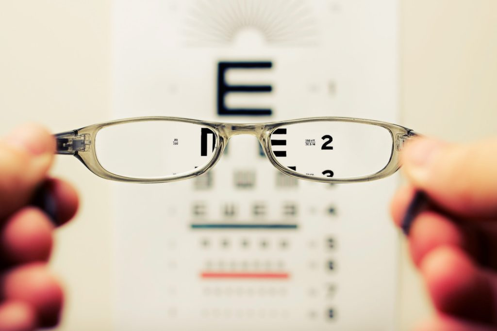 person holding eyeglasses with chart in background