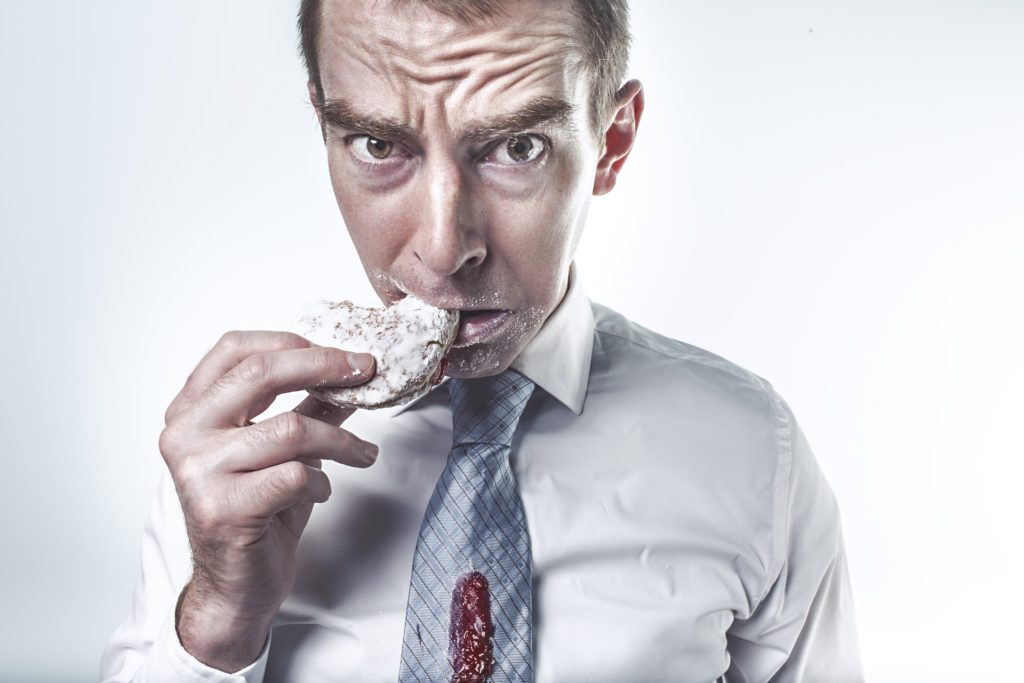 frowning man eating jelly donut